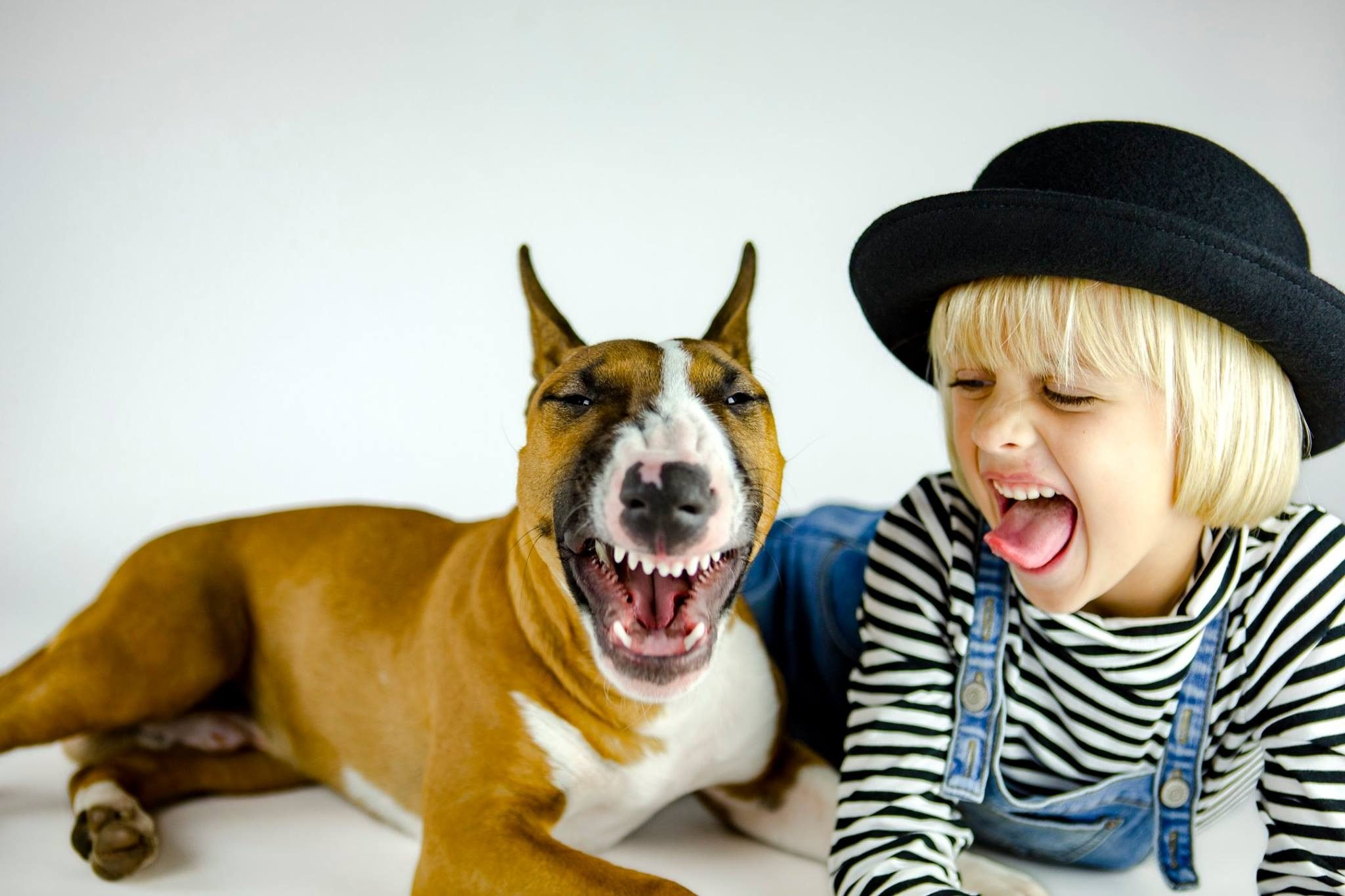 Little girl and her dog both stick their tongues out