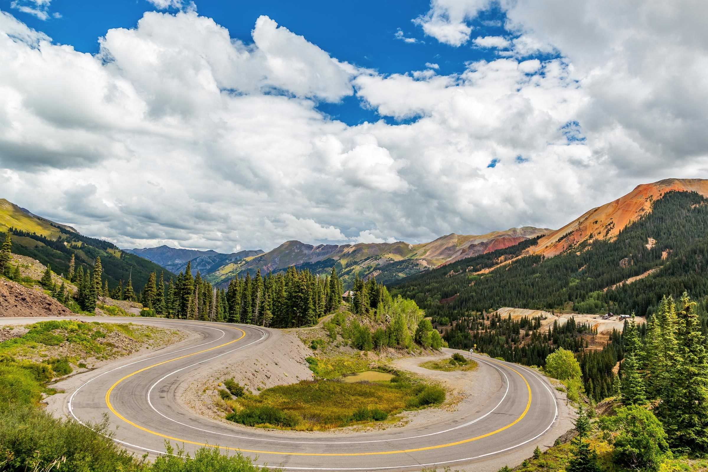 the winding road of the Million Dollar Highway, a piece of the San Juan Skyway in Colorado, with breaktaking views of the San Juan Mountains in the background