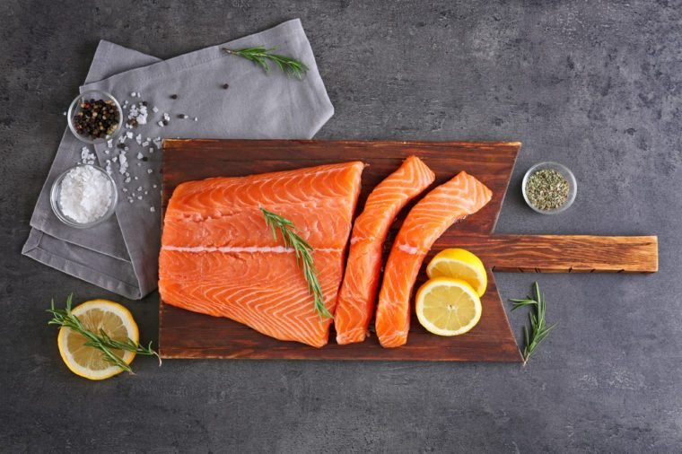 Board with fresh salmon fillet on table