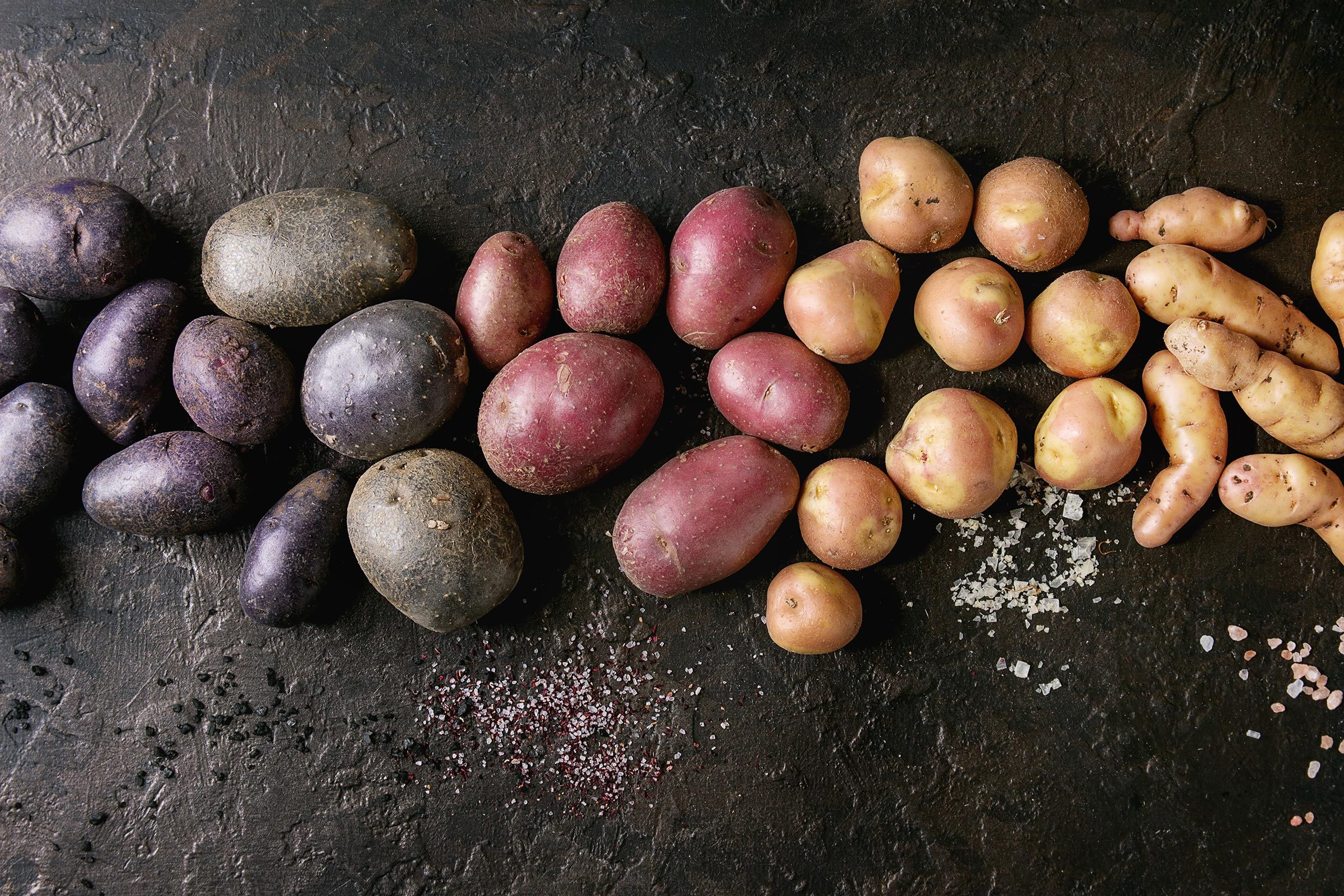 Variety of raw uncooked organic potatoes different kind and colors red, yellow, purple with various of salt over dark texture background. Top view, copy space