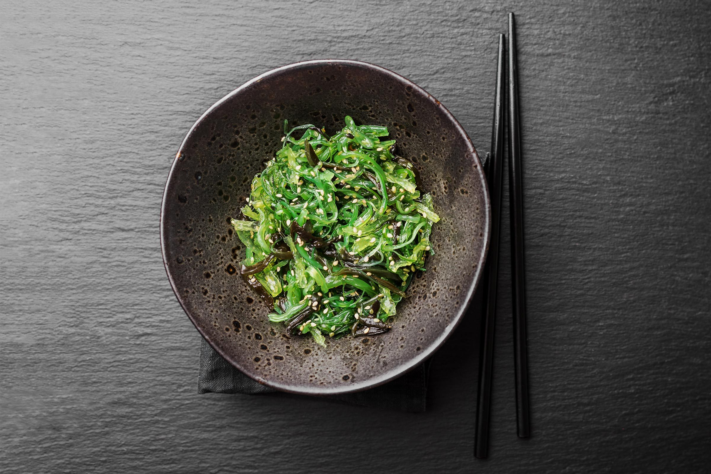Tasty appetizing seaweed salad on dark plate on slate background. Horizontal with copy space