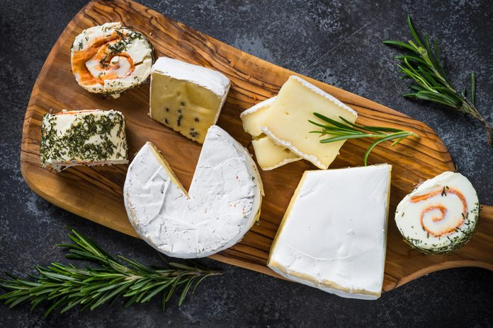 Cheese platter. Cheese assortment on cutting board. Top view on dark stone table.