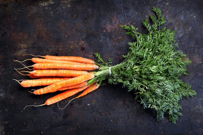 Carrot. A bunch of young carrots with parsley on a dark background.