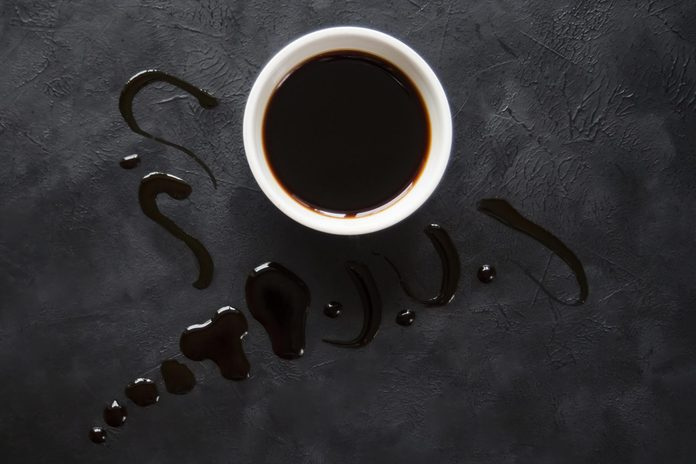 Puddle of soy sauce on a black table.