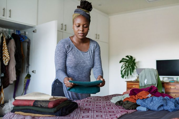 woman folding clothes and organizing her closet at home