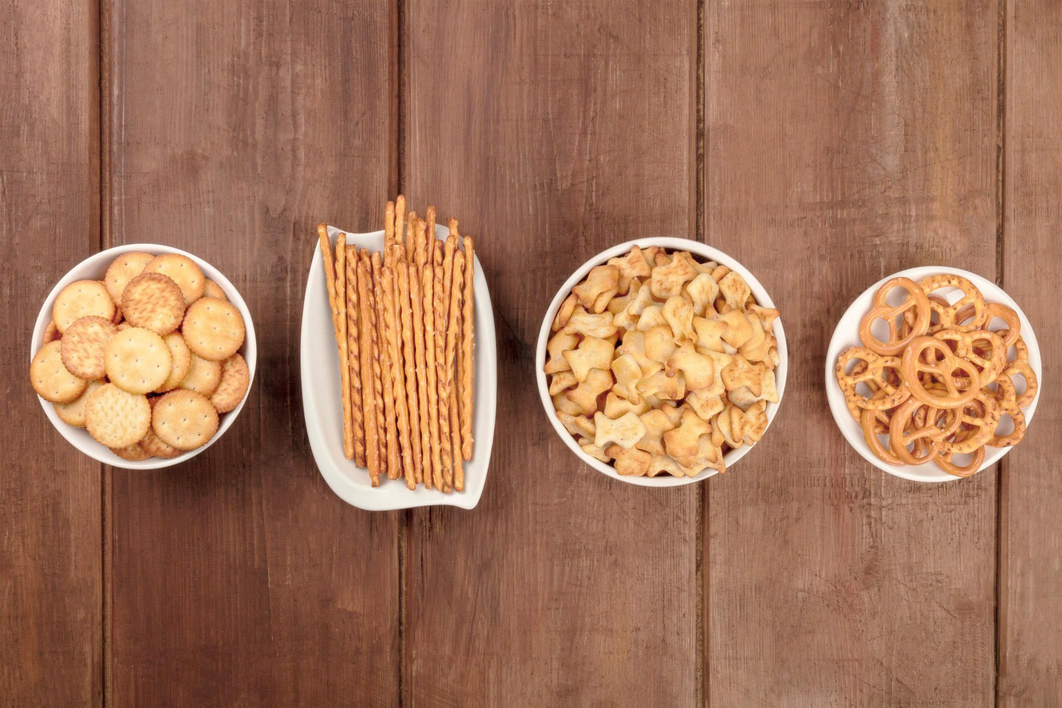 Salty crackers, sticks, pretzels, and goldfishes, shot from the top on a dark wooden background with copy space. Party snacks mix with a place for text