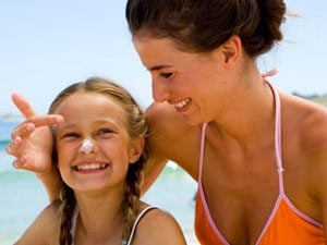 mom and daughter with sunscreen at the beach