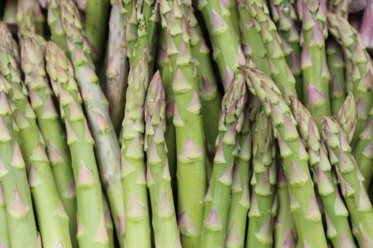 عن قرب عرض في الهواء الطلق من الهليون نصائح الصفوف. الصورة التي التقطت في السوق الفرنسية خلال فصل الربيع. نمط من عناصر الخضروات الخضراء والأصفر والأرجواني رقيقة. صورة طبيعية مجردة. الملمس الخام.