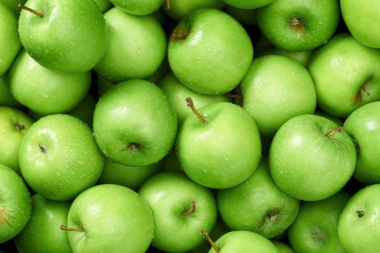 تفاحة خضراء من خلفيات الخضار والفواكه الخام من منظور علوي ، جزء من مجموعة من المنتجات الطازجة العضوية الصحية