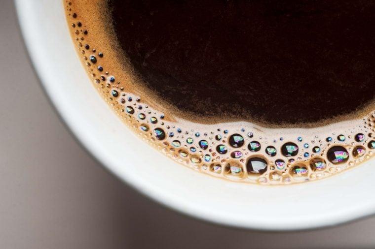 كوب أبيض من القهوة السوداء من فوق. المنظر العلوي، بسبب، قهوة الفقاعة، رفع على مقربة. فقاعة الكافيين معزولة.