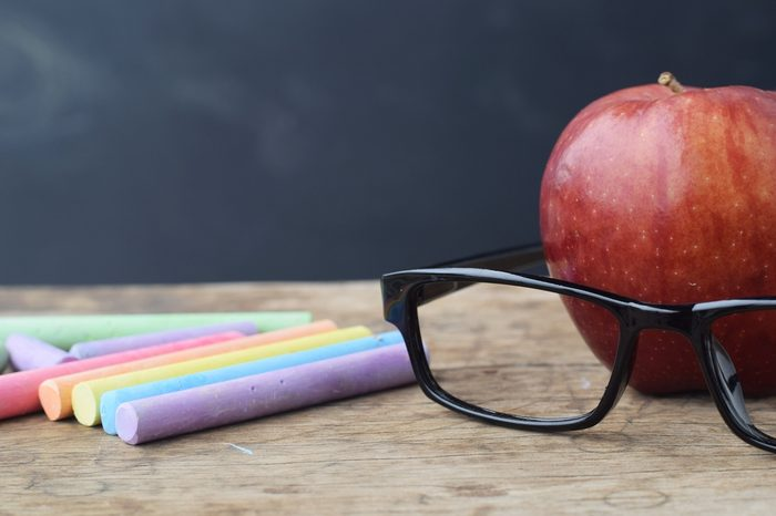 red apple with black glasses and chalk sticks on rustic wood table background, smart education or teacher's day concept