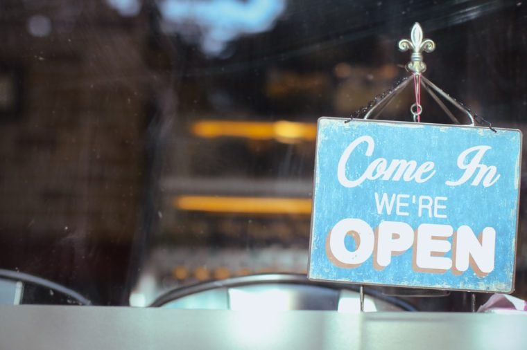 Open sign board close up through the glass of a window at coffee shop window. Shallow depth of field.