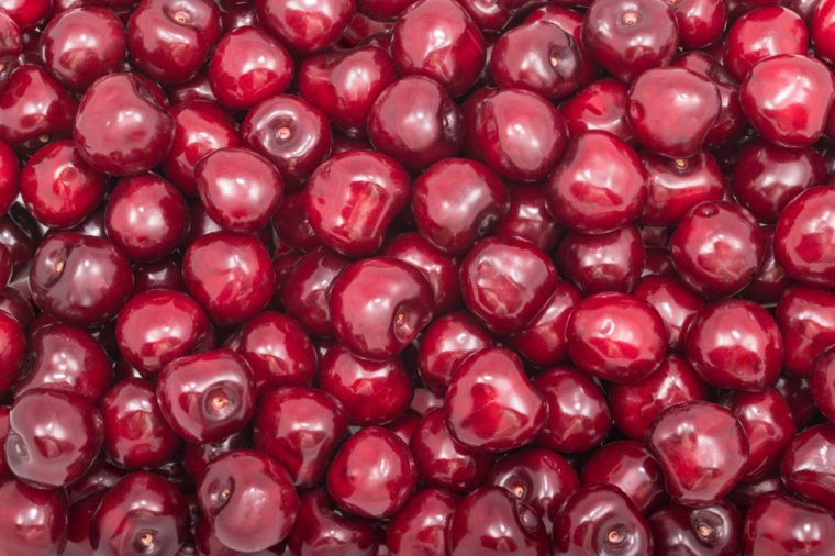 Beautiful texture of fresh cherry fruits. Prunus avium. Red fruity background. Pile of sweet ripe cherries full of vitamins, antioxidants and a delicious juice. Tasty and healthy vegetarian dessert.