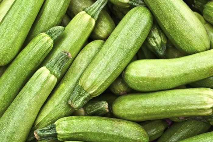 Light green fresh zucchini stacked in a heap shot from above