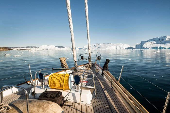 Deck of sailing ship, fjord, rear icebergs, Greenland