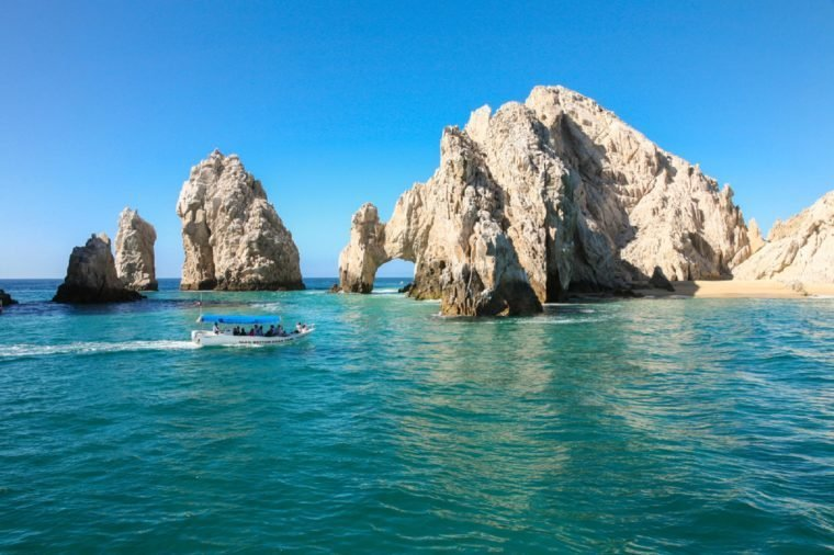 CABO SAN LUCAS, MEXICO -MARCH 20, 2012 : Boat with tourists approaching The Arch Cabo San Lucas, Mexico