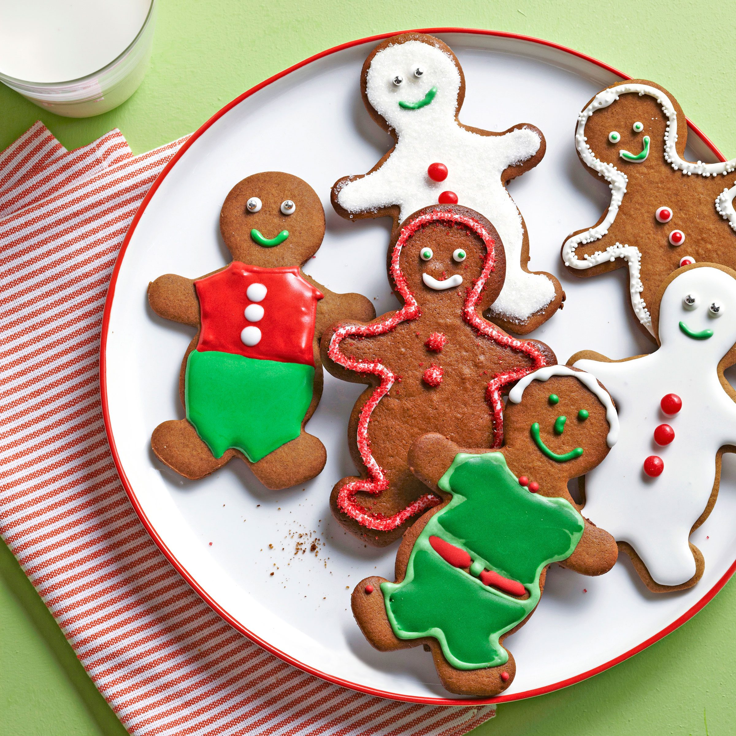 Martha Stewart's Gingerbread Men decorated cookies on a plate next to a glass of milk