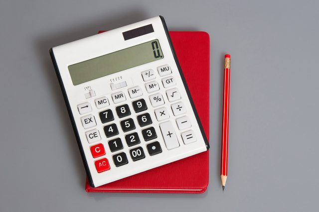 calculator, red notebook, and red pencil on gray background