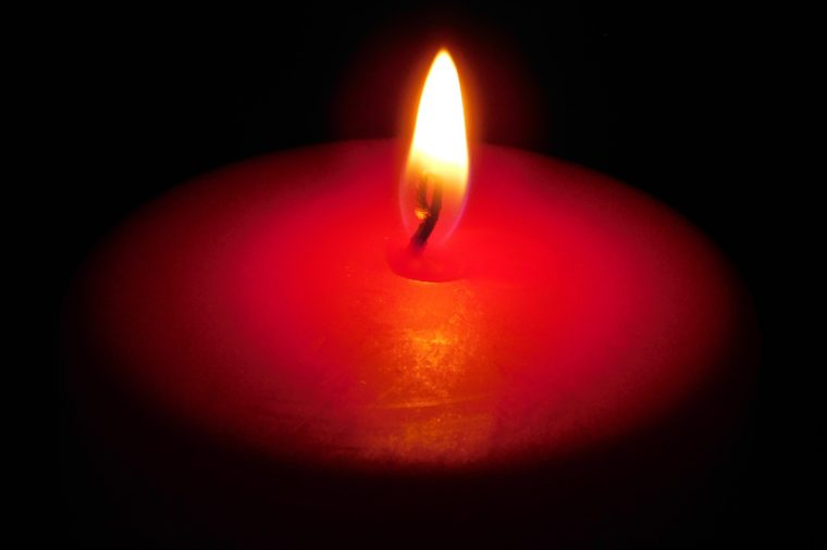 Single red candle in the darkness