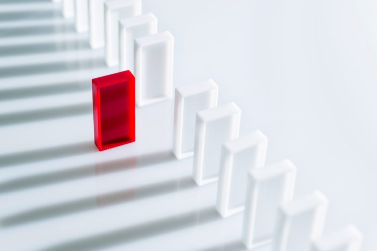 The red domino stands out among a line of white dominoes. no pips.