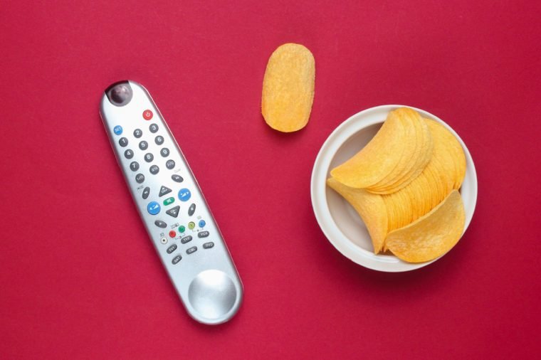 Tv remote, potato chips in a plate on red background. Watching TV, top view