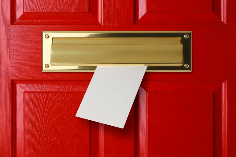 A letter coming through a gold mail slot in a red door.