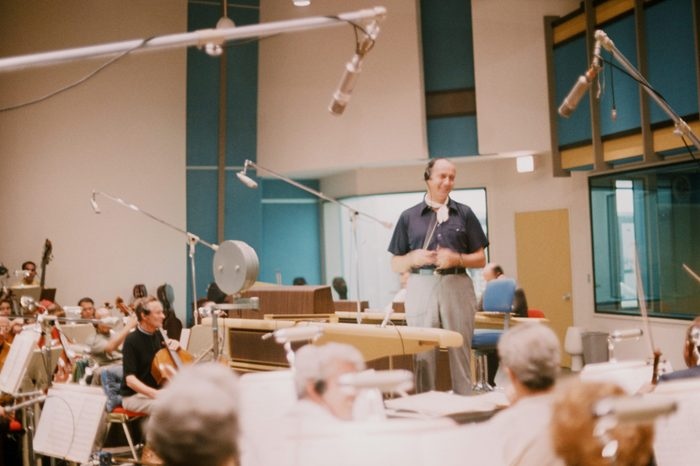 American composer and conductor Henry Mancini (born Enrico Mancini, 1924 - 1994) smiles as he stands before musicians in a studio, 1988.