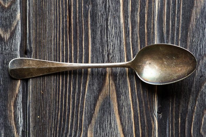 Vintage spoon on rustic wooden background