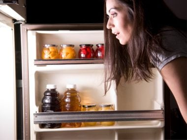 Woman opening the fridge looking for food