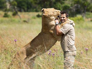 man hugging lion