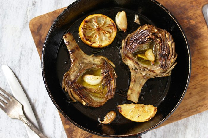 grilled artichoke with lemon in a pan. Flatlay. copy space. top view
