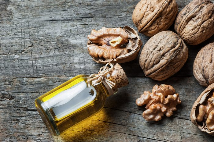 Walnut oil in glass of bottle, whole big peeled walnut kernel with thin shell on wooden background. healthy food for brain. Fresh walnuts background nut concept