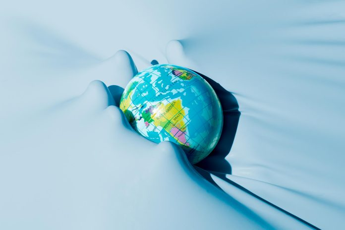 ghostly hand pushing through the background to hold the round globe of the earth