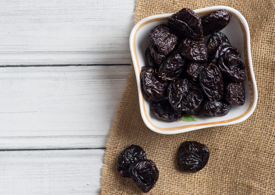 Prunes in bowl on wooden white background