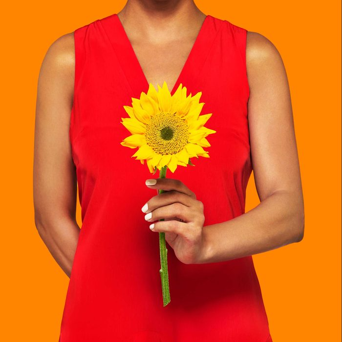 anonymous figure in a red dress holding a single sunflower