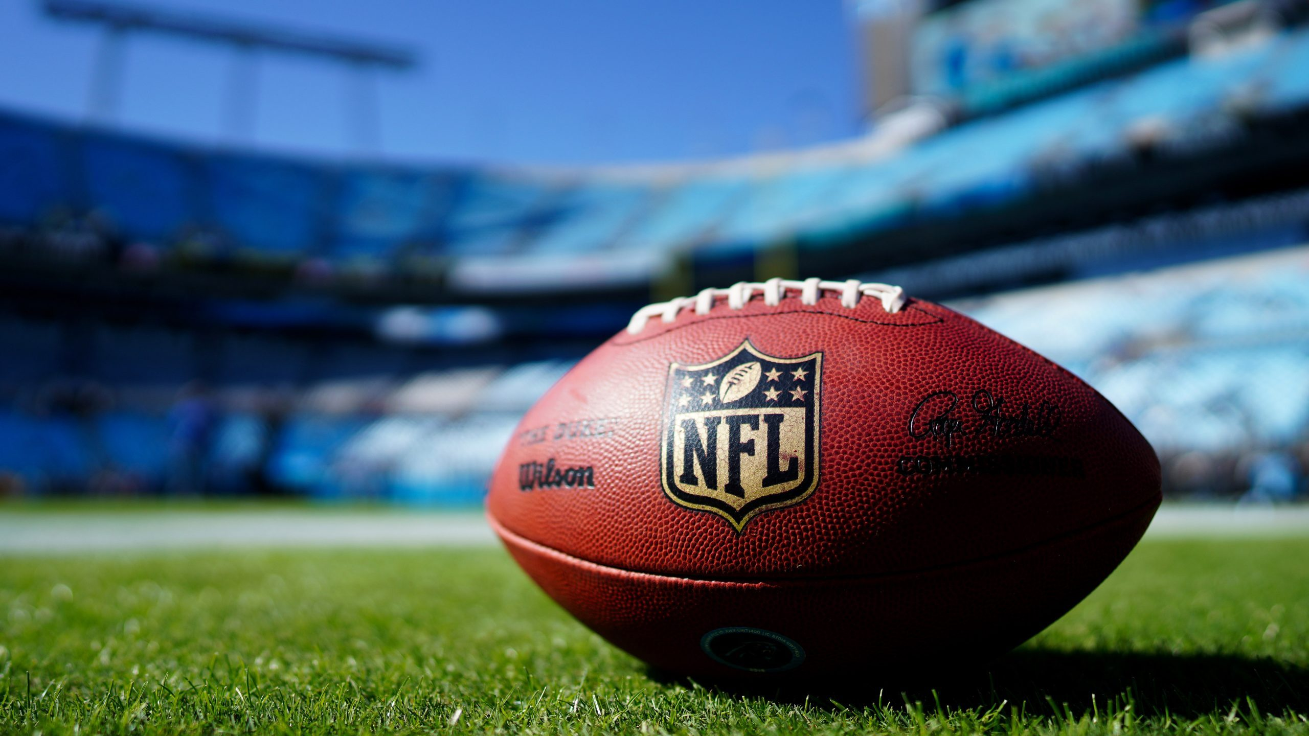 close up of nfl football on grass with blurred empty stadium in background. super bowl.