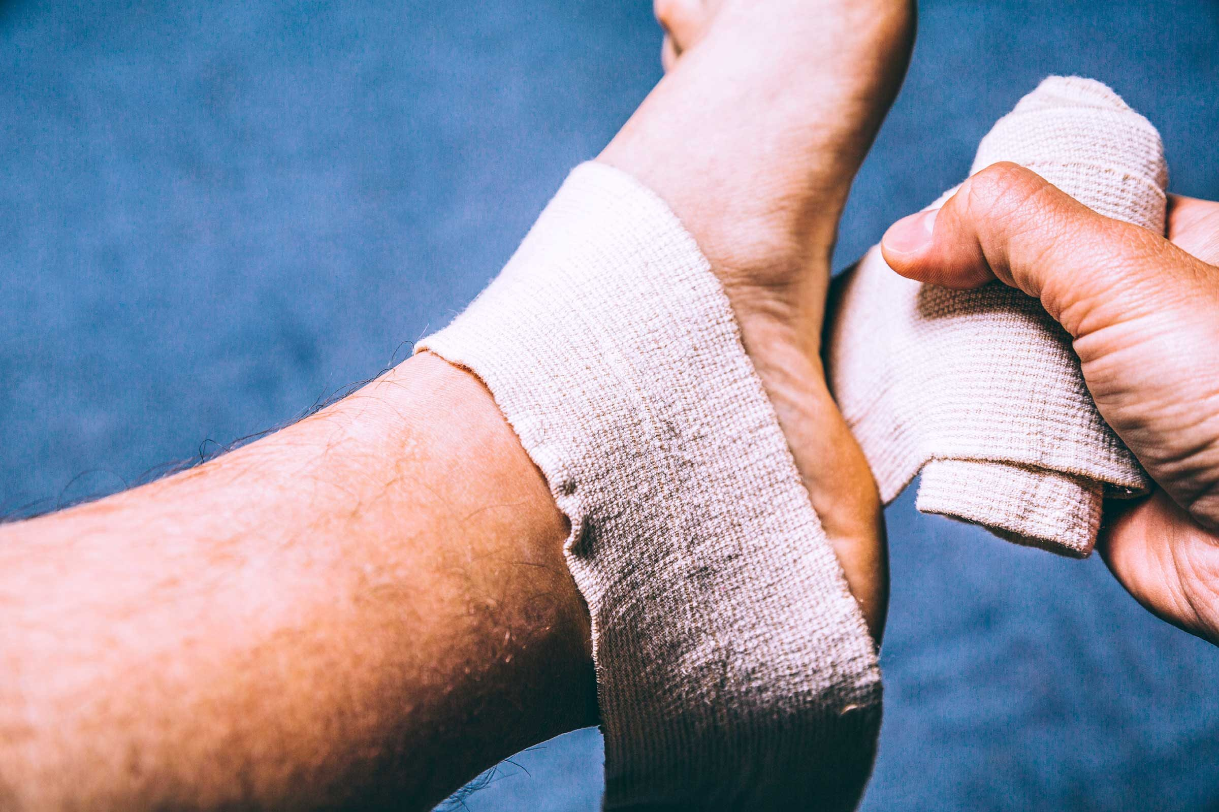 Muscle pain relief, man wrapping foot in tensor bandage