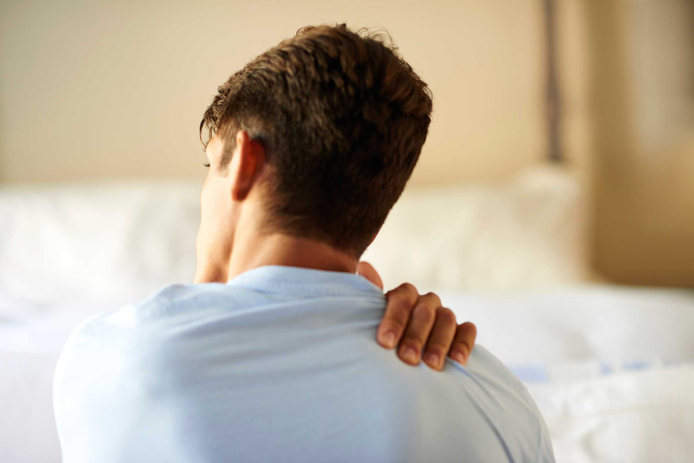Muscle pain relief, man holds sore shoulder