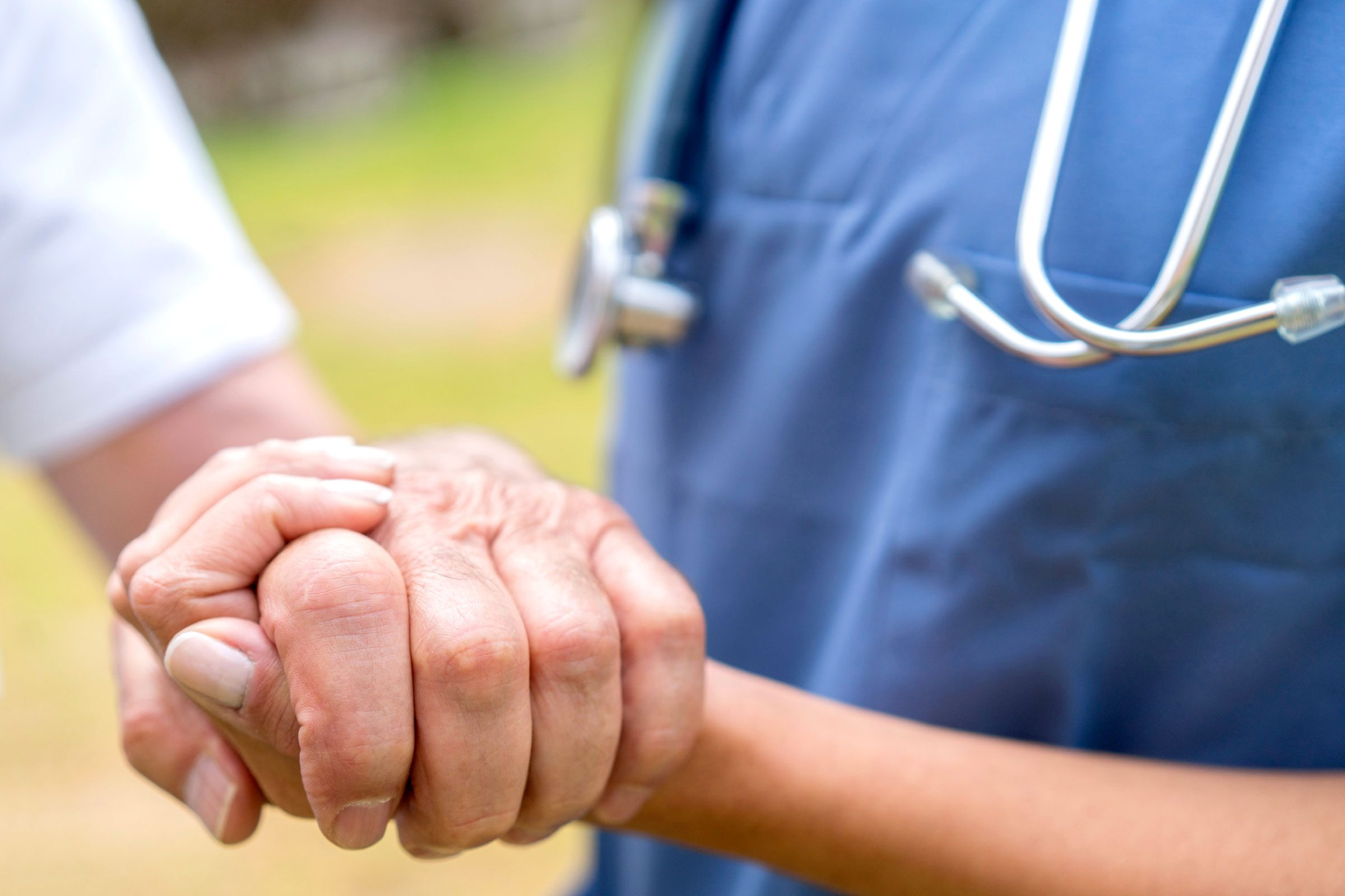 worker with stethoscope holding patient's hand