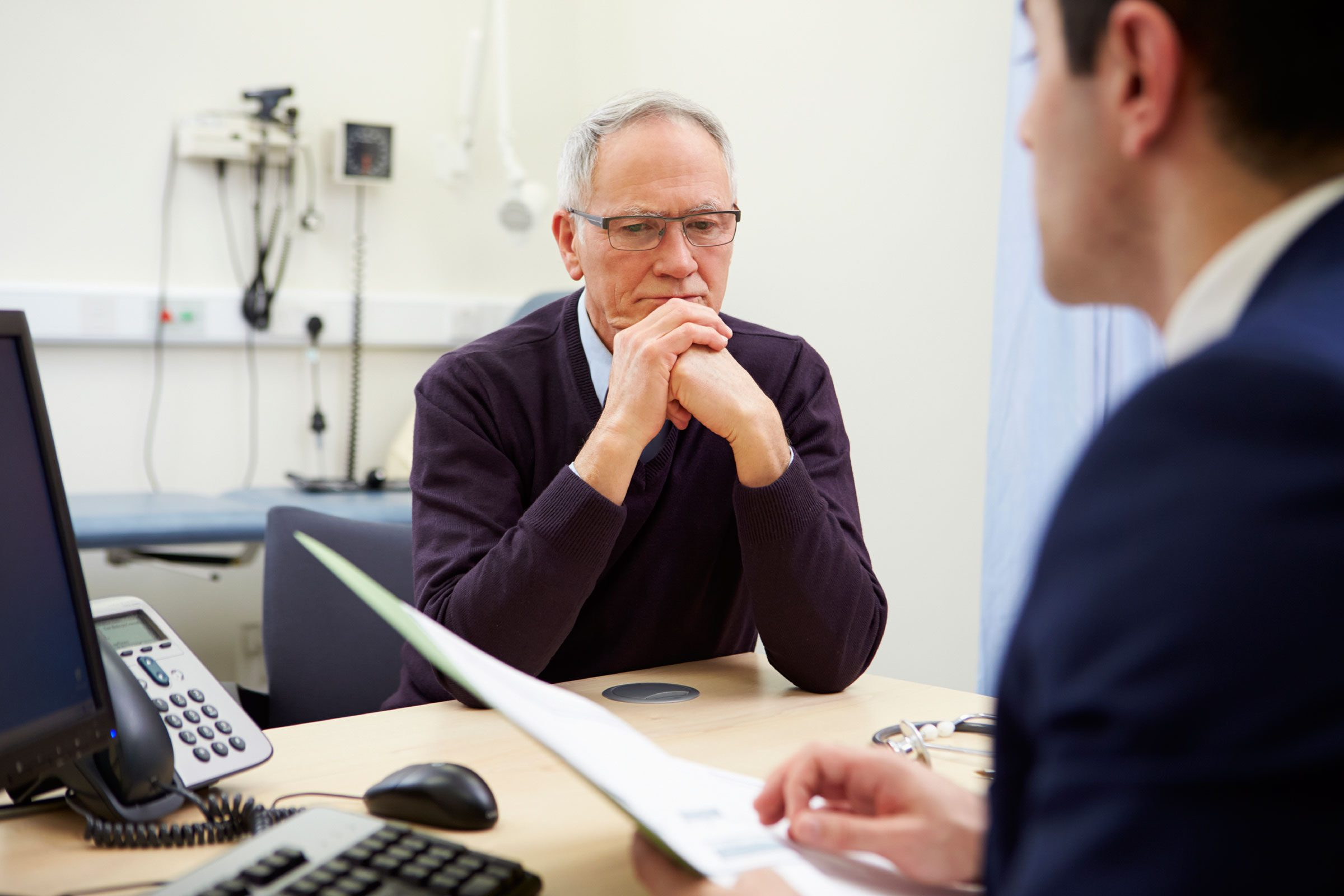 healthcare worker talking to patient at desk