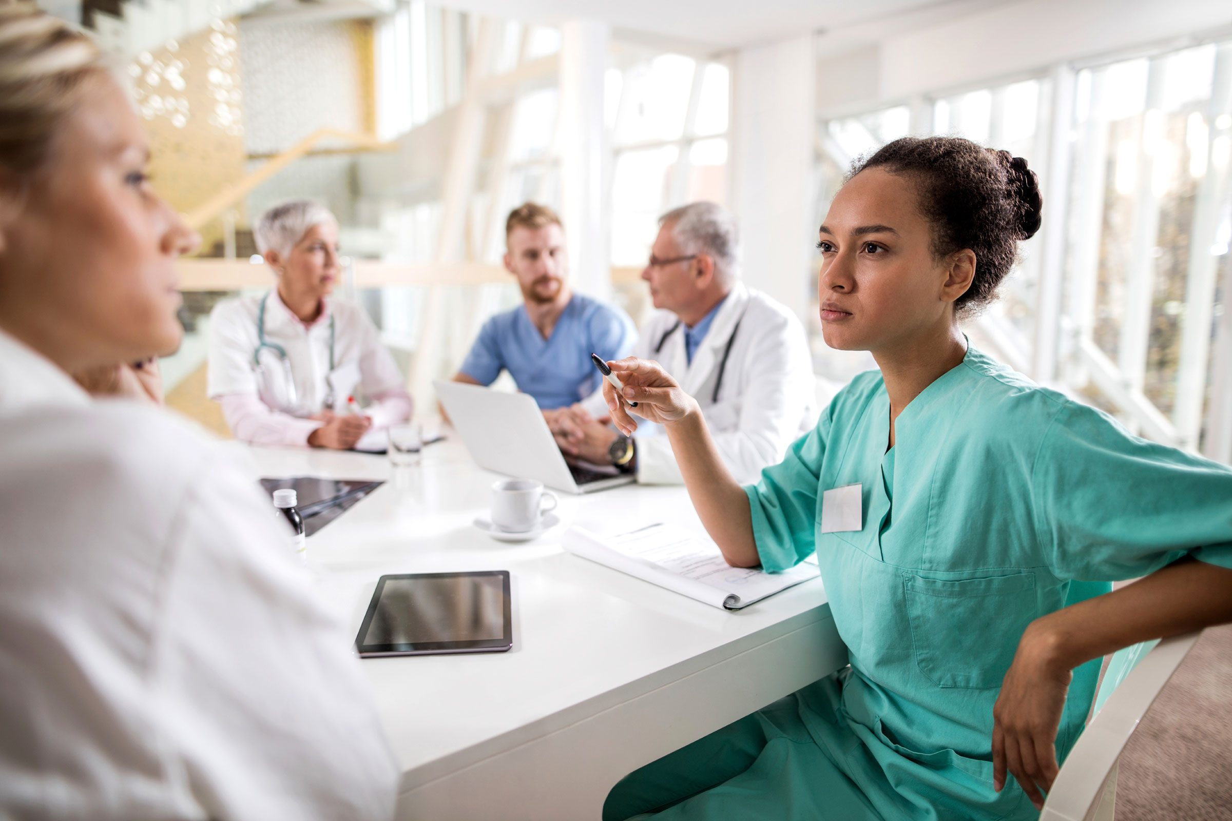 doctors and nurses talking at table