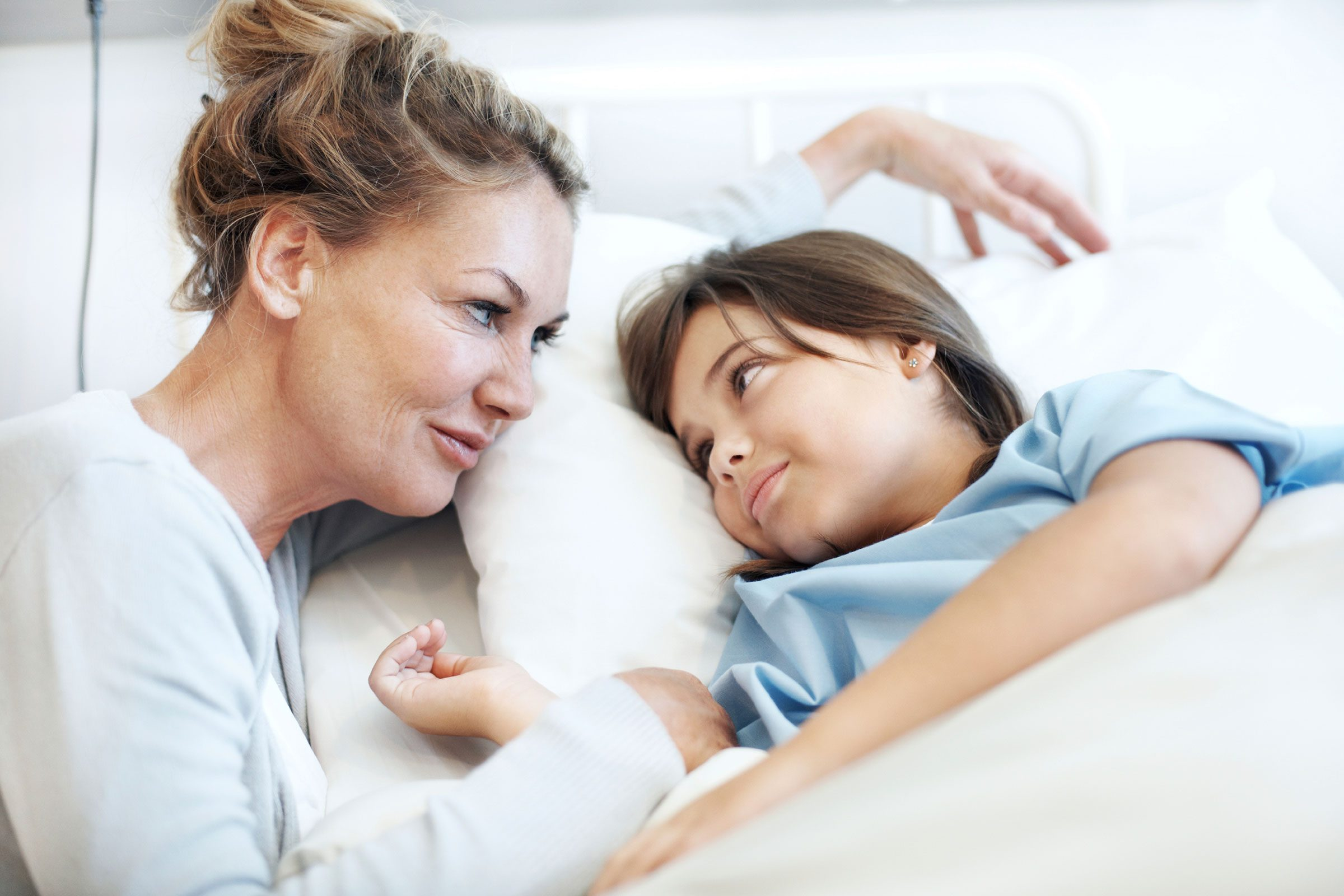 mom looking at daughter in hospital bed