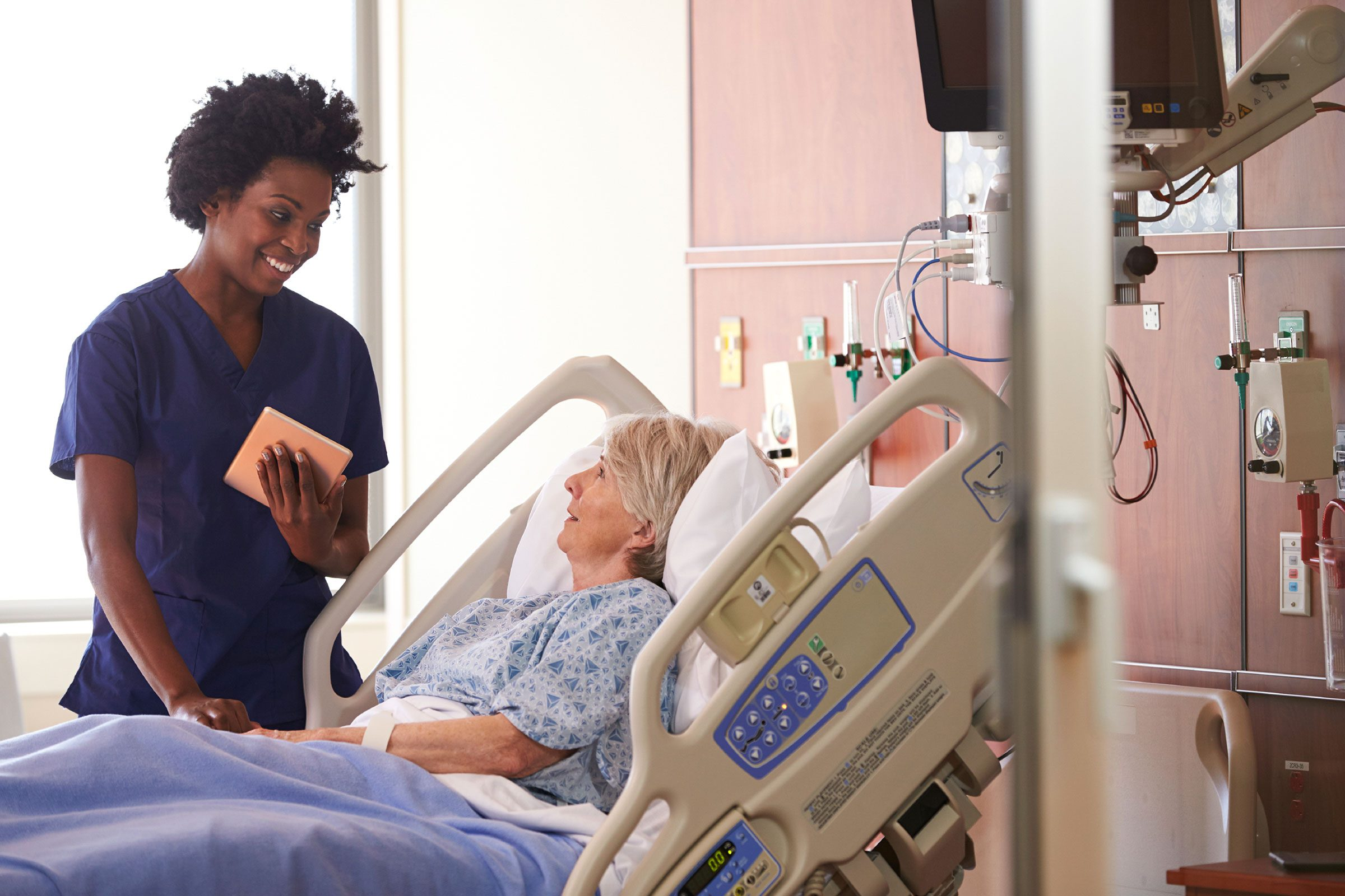 nurse smiling at patient in hospital bed