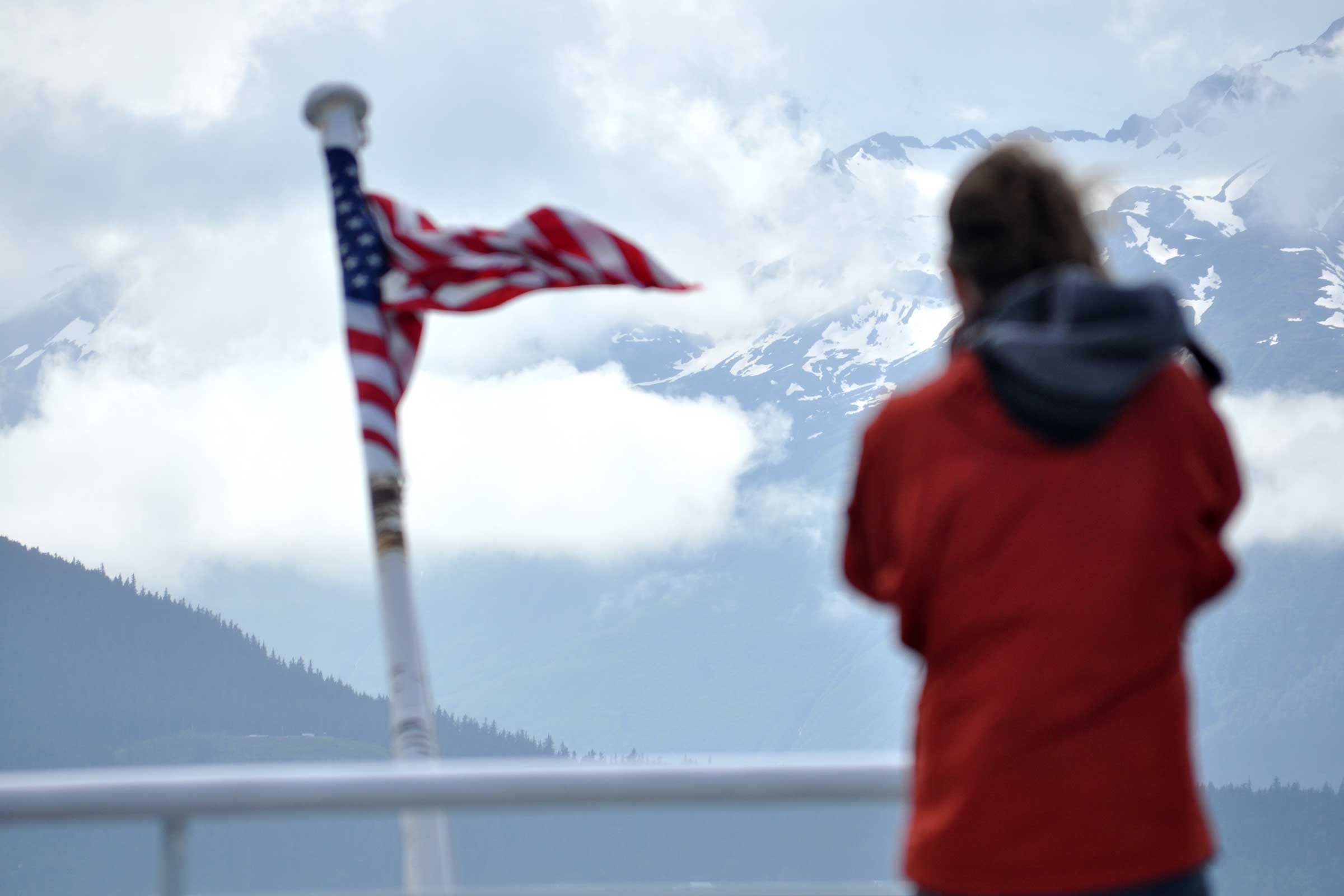 a figure braves the wind to gaze upon an american flag with mountains in the background