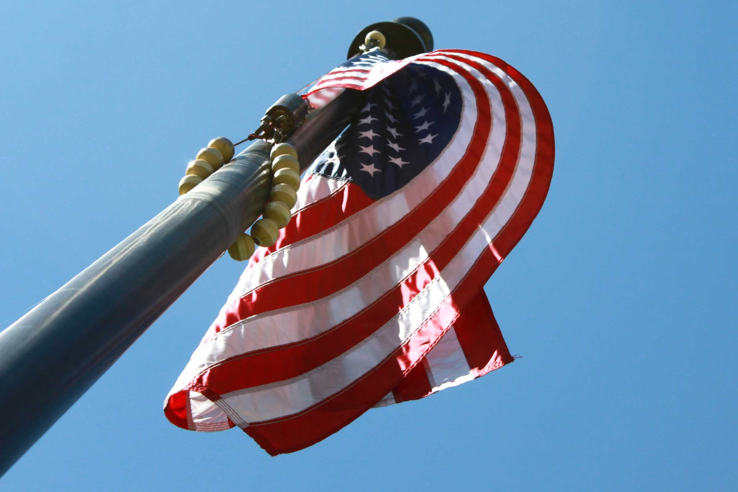 an upward view of an american flag draped in a gentle curl around its flagpole outside the historic courthouse in Hamilton County, Indiana