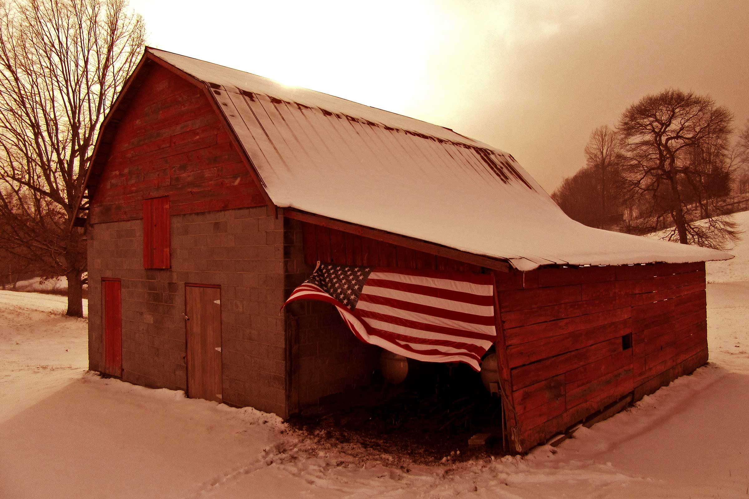 a large american flag waves on the side of a red barn in a snowy landscape in Cool Ridge, West Virginia