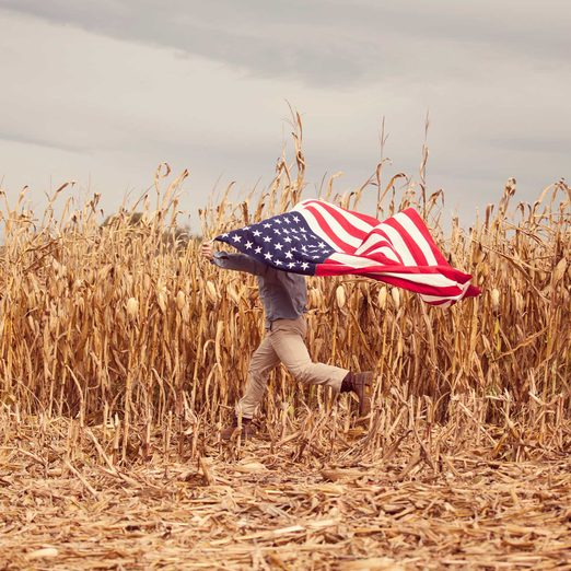 a retired Marine runs across his family's cornfield in Harrisonburg, Virginia holding an american flag above his head