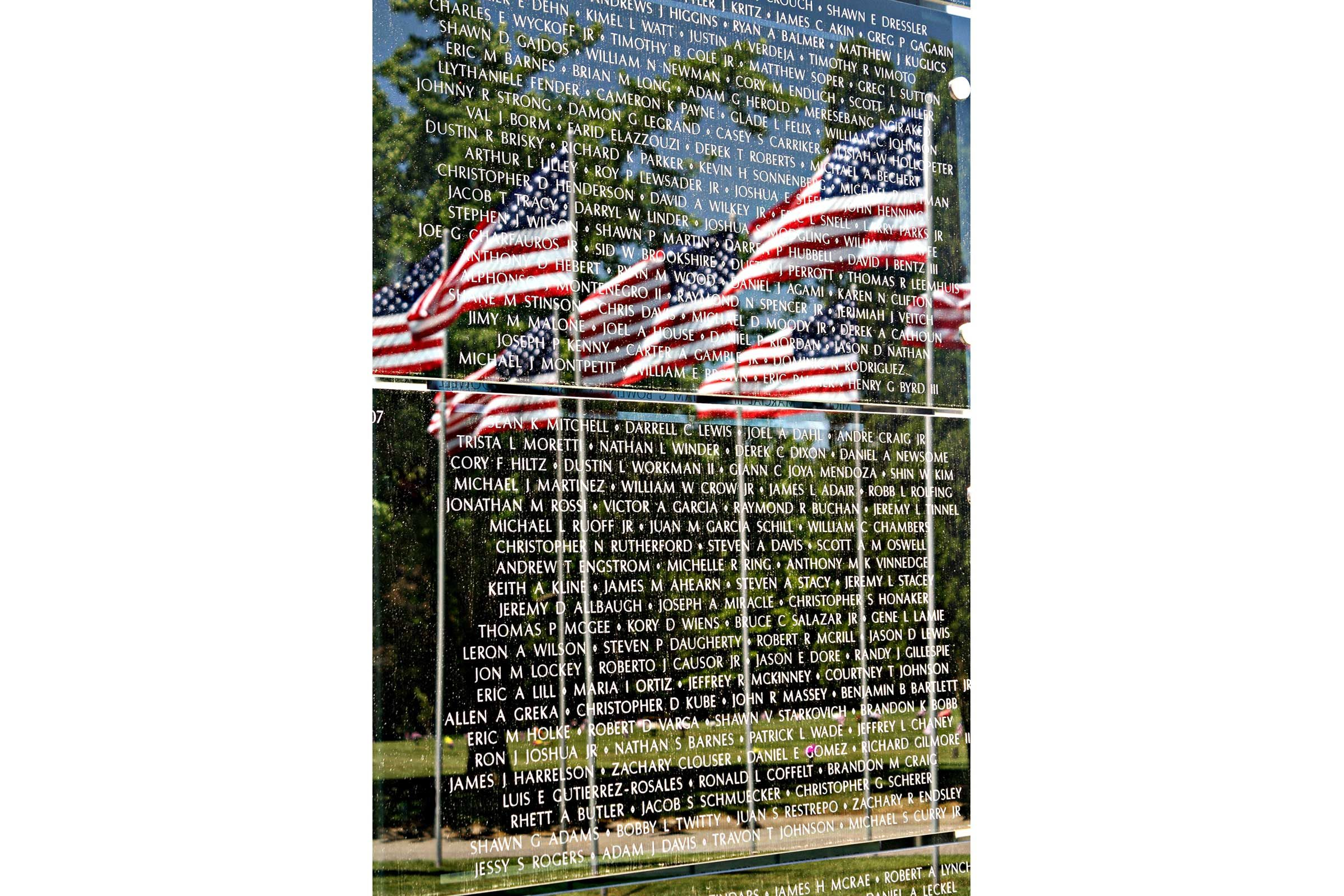 american flags reflected in the glossy surface of a memorial listing the names of those to be remembered