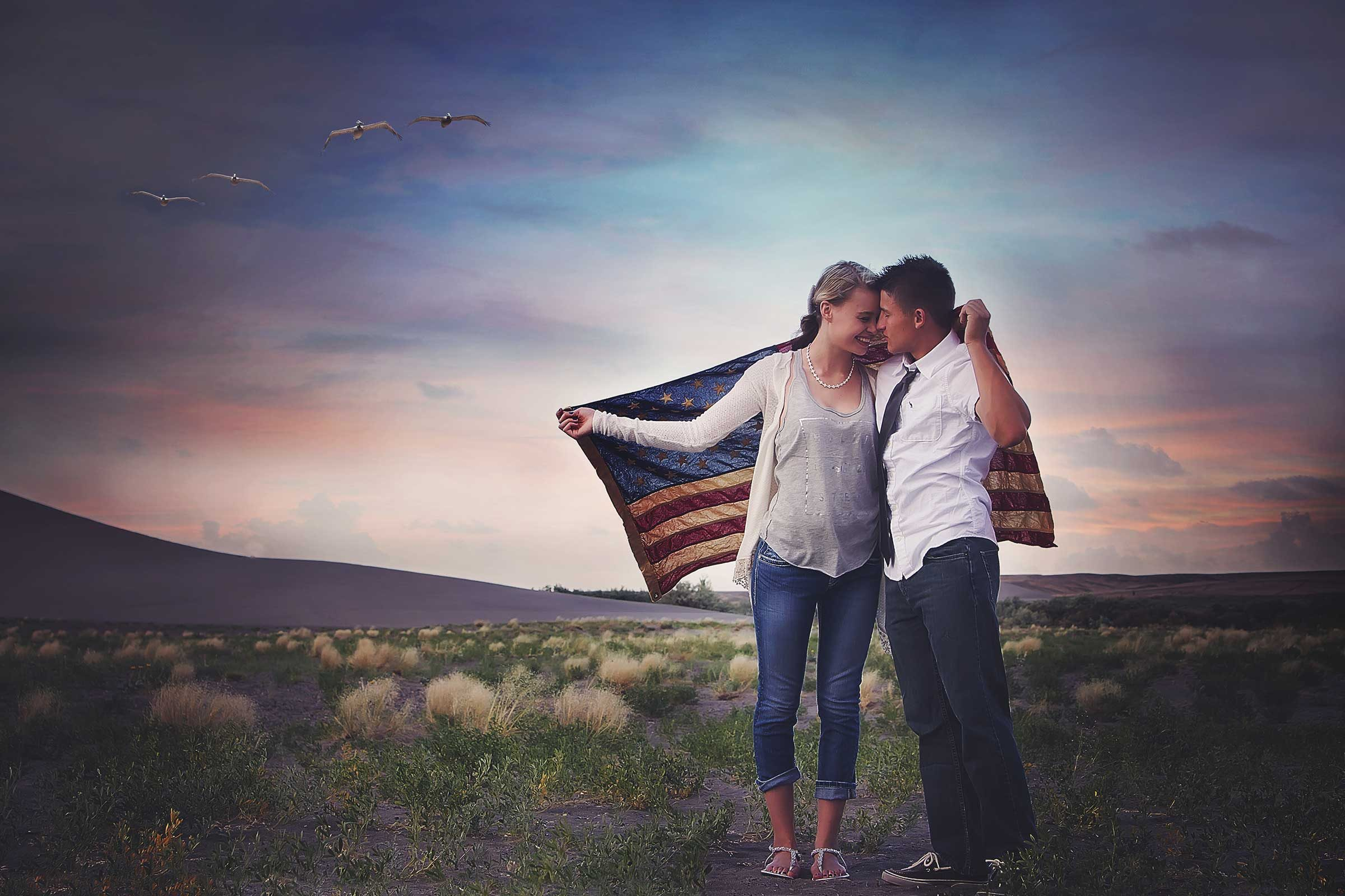 portrait of a couple holding the american flag around themselves standing in a landscape at sunset