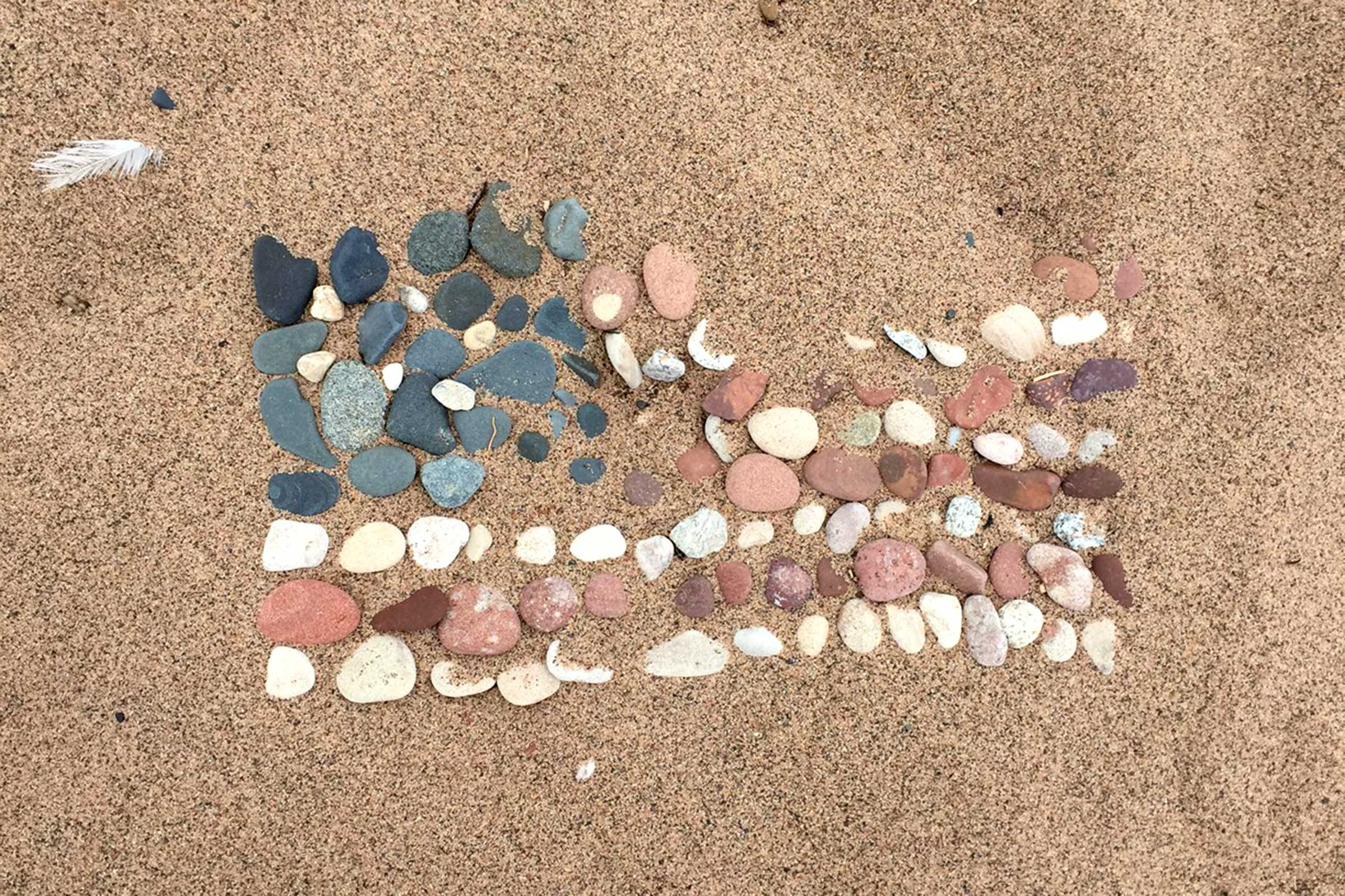 an array of rocks in the sand along the Wisconsin shore of Lake Superior create the image of an american flag